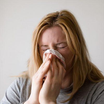 kvinde nyser, med lommetoerklaede